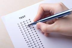 Sluit omhoog van hand het vullen het blad van de testscore met antwoorden Stock Afbeeldingen