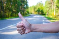 Sluit omhoog van hand hitching auto op weg Royalty-vrije Stock Foto