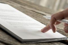 Sluit omhoog van hand met buitensporige pen op document Royalty-vrije Stock Foto