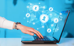 Sluit omhoog van hand met laptop en sociale media pictogrammen Royalty-vrije Stock Foto's
