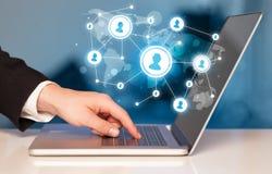Sluit omhoog van hand met laptop en sociale media pictogrammen Stock Foto