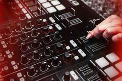 Sluit omhoog van hand stijgend geluid van instrument van DJ, die fader het bewegen zich royalty-vrije stock afbeelding