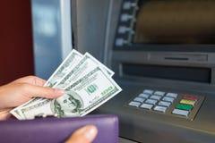 Sluit omhoog van hand terugtrekt geld bij ATM-machine stock afbeeldingen
