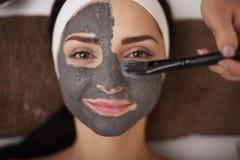 Sluit omhoog van hand toepassend gezichtsmasker op vrouwengezicht bij schoonheid sa Royalty-vrije Stock Afbeelding