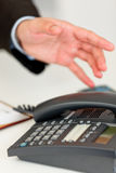 Sluit omhoog van hand zich uitbreidt tot bureautelefoon Stock Afbeeldingen