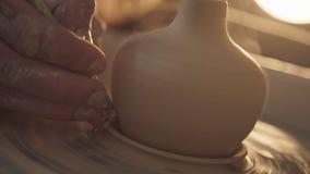 Sluit omhoog van handen die klei werken aan pottenbakkers` s wiel stock videobeelden