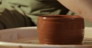 Sluit omhoog van handen die klei werken aan pottenbakkers` s wiel, close-upmening stock footage