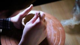 Sluit omhoog van handen die klei werken aan pottenbakkers` s wiel De pottenbakker vormt het kleiproduct met aardewerkhulpmiddelen stock video