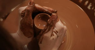 Sluit omhoog van handen die klei werken aan pottenbakkers` s wiel, Hoogste mening, close-upmening stock videobeelden