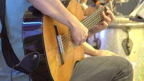 Sluit omhoog van handen van een mens die een klassieke gitaar op stadium spelen stock videobeelden