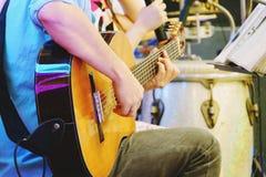 Sluit omhoog van handen van een mens die een klassieke gitaar op stadium spelen royalty-vrije stock fotografie