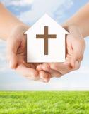 Sluit omhoog van handen en document huis met kruis Stock Foto
