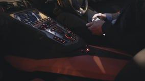 Sluit omhoog van handen gebruikend digitale tablet terwijl het zitten in een auto voorraad De zakenman controleert de aandelen op stock videobeelden