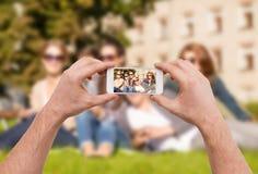 Sluit omhoog van handen makend beeld van groep tienerjaren Stock Afbeeldingen