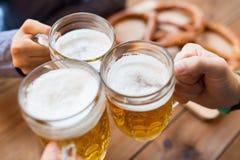 Sluit omhoog van handen met biermokken bij bar of bar Stock Afbeeldingen
