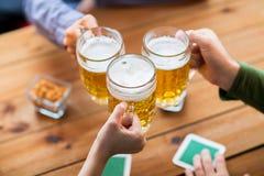 Sluit omhoog van handen met biermokken bij bar of bar Stock Afbeelding