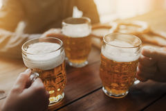 Sluit omhoog van handen met biermokken bij bar of bar Stock Foto