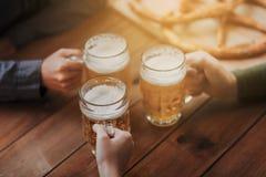 Sluit omhoog van handen met biermokken bij bar of bar Stock Fotografie