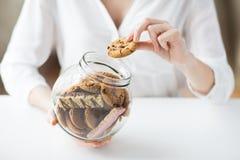 Sluit omhoog van handen met chocoladekoekjes in kruik Stock Afbeeldingen