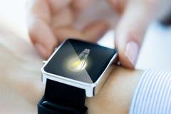 Sluit omhoog van handen met lightbulb op smartwatch Stock Afbeeldingen