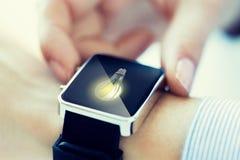 Sluit omhoog van handen met lightbulb op smartwatch Stock Fotografie