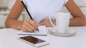 Sluit omhoog van handen met pen schrijvend aan blocnote met koffie en smartphone op de lijst royalty-vrije stock afbeelding