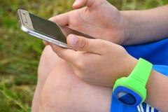 Sluit omhoog van handen met slim telefoon en horloge royalty-vrije stock afbeelding