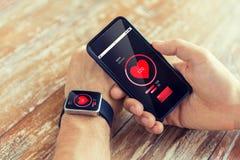 Sluit omhoog van handen met slim telefoon en horloge stock afbeelding