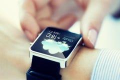 Sluit omhoog van handen met weerpictogram op smartwatch Stock Foto's