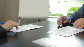 Sluit omhoog van handen van zakenlieden die contract in langzame motie ondertekenen stock footage