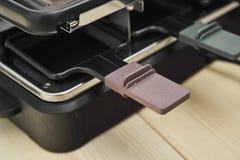 Sluit omhoog van handvatdienbladen van een raclettemachine Stock Fotografie