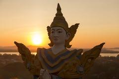 Sluit omhoog van het Birmaanse jonge standbeeld van Boedha met zonsondergang royalty-vrije stock fotografie