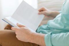 Sluit omhoog van het boek van de mensenlezing thuis Stock Fotografie