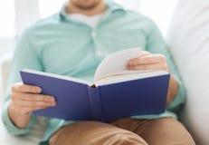 Sluit omhoog van het boek van de mensenlezing thuis Royalty-vrije Stock Fotografie