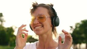 Sluit omhoog van het eerlijke haarmeisje dansen aan het ritme van muziek met hoofdtelefoons Vooraanzicht van een gelukkig wijfje  stock footage