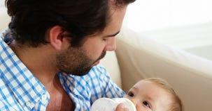 Sluit omhoog van het gelukkige vader met de fles grootbrengen aan zijn baby stock videobeelden