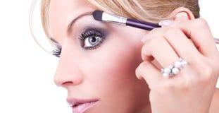 Sluit omhoog van het gezicht van meisjesverven met make-up Stock Fotografie