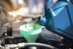 Sluit omhoog van het Gieten van verse olie aan motor van een auto in autoreparatieservi royalty-vrije stock foto's