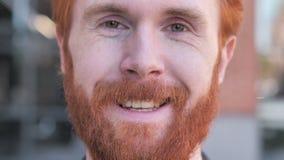 Sluit omhoog van het Glimlachen de Jonge Mensengezicht van de Roodharigebaard stock videobeelden