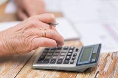Sluit omhoog van het hogere vrouw tellen met calculator Stock Foto's