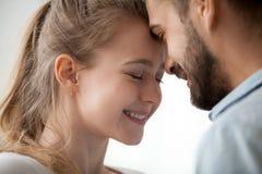 Sluit omhoog van het houden van van paar die wat betreft voorhoofd van tederheid genieten stock afbeelding