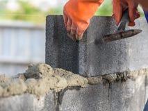 Sluit omhoog van het installeren van bakstenen in bouwwerf door industriële metselaar royalty-vrije stock foto's
