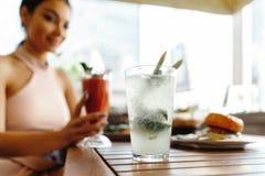 Sluit omhoog van het jonge aantrekkelijke glas van de vrouwenholding met smoothie bij straatkoffie stock foto's