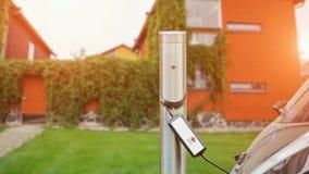 Sluit omhoog van het laden post Een kabel wordt verbonden met de post, die een elektrische auto laadt stock videobeelden