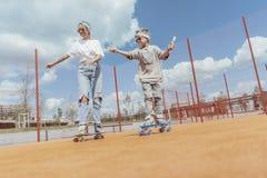 Sluit omhoog van het met een skateboard rijden van familie bij speelplaats Gelukkig familieconcept royalty-vrije stock foto