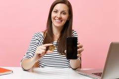 Sluit omhoog van het metaalmuntstuk van de vrouwenholding bitcoin van gouden kleur, toekomstige munt en mobiele telefoon met het  royalty-vrije stock foto's