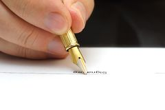 Sluit omhoog van het ondertekenen van document met vulpen Stock Foto's