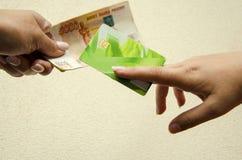 Sluit omhoog van het ruilen van of het overbrengen van een creditcard en bankbiljetten naar een andere persoon Het concept van he stock foto
