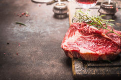 Sluit omhoog van het ruwe Lapje vlees van vers vleesribeye met kruiden en kruiden op donkere rustieke metaalachtergrond Stock Fotografie