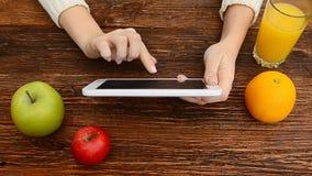 Sluit omhoog van het scherm van tabletpc met vruchten en jus d'orange op de lijst stock videobeelden